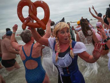 Orang-orang dengan mengenakan kostum warna-warni menyerbu perairan Laut Utara  untuk merayakan akhir pekan pertama Januari 2020 di Ostend, Belgia, Sabtu (4/1/2020). Cuaca dingin tak menghalangi mereka untuk menceburkan diri ke laut yang merupakan salah satu tradisi tahun baru.  (AP/Francisco Seco)