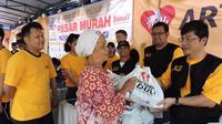 Koordinator Pasar Murah Artha Graha Peduli Jet Soedirdja, menyerahkan langsung paket sembako murah kepada warga di dampingi oleh Ketua Pelaksana Pasar Murah Arviano Sahar (sebelah kiri), Jakarta, Minggu (24/1/2014). (Media Center AGN - AGP)