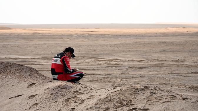 Pembalap asal Spanyol, Fernando Alonso duduk di atas pasir saat panitia menetralisasi omba Reli Dakar 2020 menyusul angin kencang yang mewarnai etape ke-10 dari Harardh ke Shubaytah, Arab Saudi, 15 Januari 2020. (Franck Fife/AFP).