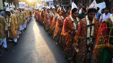 Iring-iringan calon pasangan pengantin di India saat mengikuti upacara pernikahan massal di Kolkata (14/2). Lebih dari 160 pasangan yang mengalami kesulitan ekonomi mengikuti acara nikah massal tersebut. (AFP Photo/Dibyangshu Sarkar)