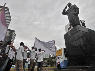 Sejumlah aktivis melakukan penghormatan sambil mengheningkan cipta di depan patung Jenderal Soedirman, Jakarta, Rabu (14/11). Aksi ini dalam rangka memperingati Hari Pahlawan dan menghormati jasa-jasa Jenderal Soedirman. (Merdeka.com/ Iqbal S. Nugroho)