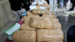 Petugas memperlihatkan barang bukti saat rilis pengungkapan sindikat narkoba jaringan internasional di Rumah Sakit Polri, Jakarta, Senin (2/12/2019). Dalam kasus ini polisi menangkap AC, narapidana Lapas Tangerang, dan EF (meninggal dunia) akibat berusaha melarikan diri. (merdeka.com/Iqbal  Nugroho)