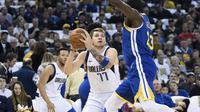 Luka Doncic (baju putih) mencoba mengecoh pemain Warriors Draymond Green pada lanjutan NBA (AP)