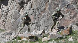 Pasukan menuruni tebing saat ikut serta dalam latihan gabungan Kyrgyzstan dan India di Ngarai Tatyr, selatan Bishkek, dekat Desa Arashan, Kyrgyzstan, Senin (26/4/2021). Pasukan tersebut berlatih untuk mengoordinasikan aksi mereka melawan militan. (AP Photo/Vladimir Voronin)