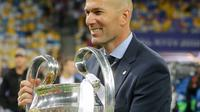 Pelatih Real Madrid Zinedine Zidane memegang trofi usai menjadi juara Liga Champions 2018 di Stadion NSK Olimpiyskiy, Ukraina (26/5). Real Madrid berhasil menjadi juara Liga Champions 2018 usai mengalahkan Liverpool 3-1. (AP/Sergei Grits)
