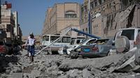 Seorang pria berjalan melewati puing-puing gedung yang runtuh di kompleks kepresidenan, di Sanaa, Yaman (7/5). Akibat serangan ini sedikitnya enam orang tewas dan sekitar 30 orang terluka. (AP Photo/Hani Mohammed)