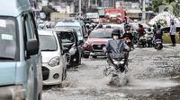 Sejumlah kendaraan terjebak kemacetan akibat banjir yang menggenangi Jalan Jatinegara Barat, Jakarta, Senin (8/2/2021). Banjir yang menggenangi Jalan Jatinegara Barat terjadi akibat luapan Kali Ciliwung yang dipicu hujan deras di Jakarta dan Bogor sejak dini hari tadi. (merdeka.com/Iqbal S. Nugroho)