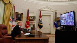 Presiden AS Donald Trump berbicara dengan prajurit militer melalui konferensi video di Gedung Putih, Selasa (25/12). Prajurit tersebut ditempatkan di Guam, Qatar, Alaska, dan dua kelompok di Bahrain. (AP Photo/Jacquelyn Martin)
