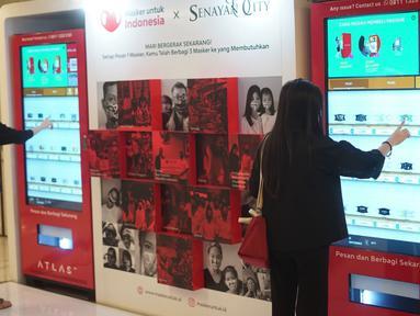 Pengunjung membeli masker dari mesin penjual otomatis (vending machine) di Senayan City, Jakarta, Jumat (6/11/2020). Penyediaan dua mesin penjual masker otomatis tersebut bertujuan memudahkan pengunjung untuk dapat membeli masker di dalam mal. (Liputan6.com/Immanuel Antonius)