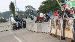Pengendara motor menerobos beton pembatas di kawasan lingkar Stadion Pakansari, Kabupaten Bogor, Jawa Barat, Rabu (10/6/2020). Hingga Rabu (10/6), Pemkab Bogor masih menutup kawasan Stadion Pakansari untuk semua kegiatan sebagai upaya pencegahan penyebaran COVID-19. (Liputan6.com/Helmi Fithriansyah)