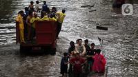 Warga melintasi banjir yang merendam kawasan Green Garden, Jakarta Barat, Selasa (25/2/2020). Hujan yang mengguyur kawasan Jakarta membuat kawasan tersebut tergenang banjir setinggi 60-80 cm. (Liputan6.com/Johan Tallo)