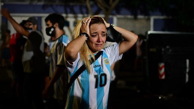 Fans legenda sepak bola Argentina Diego Maradona menangis saat berkumpul dengan penggemar lain untuk memberi penghormatan pada hari kematiannya di Argentinos Junior's Diego Armando Maradona Stadium di La Paternal, Buenos Aires, Argentina, 25 November 2020. (RONALDO SCHEMIDT/AFP)