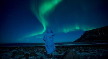 Seseorang menonton fenomena alam Aurora Borealis atau Northern Lights di Unstad, lingkaran Arktik, Norwegia, Sabtu (3/3). Aurora menampilkan banyak warna, tapi yang sering muncul adalah hijau muda dan pink. (Olivier MORIN/AFP)