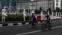 """Pesepeda melintasi puluhan boneka maneken yang dipajang di Bundaran HI, Jakarta, Minggu (15/11/2020). Boneka maneken itu sebagai bentuk """"Mengenang Korban Kecelakaan Lalu Lintas 2020"""" dan mengingatkan pengguna jalan agar selalu patuhi peraturan lalu lintas demi keselamatan. (Liputan6.com/Johan Tallo)"""