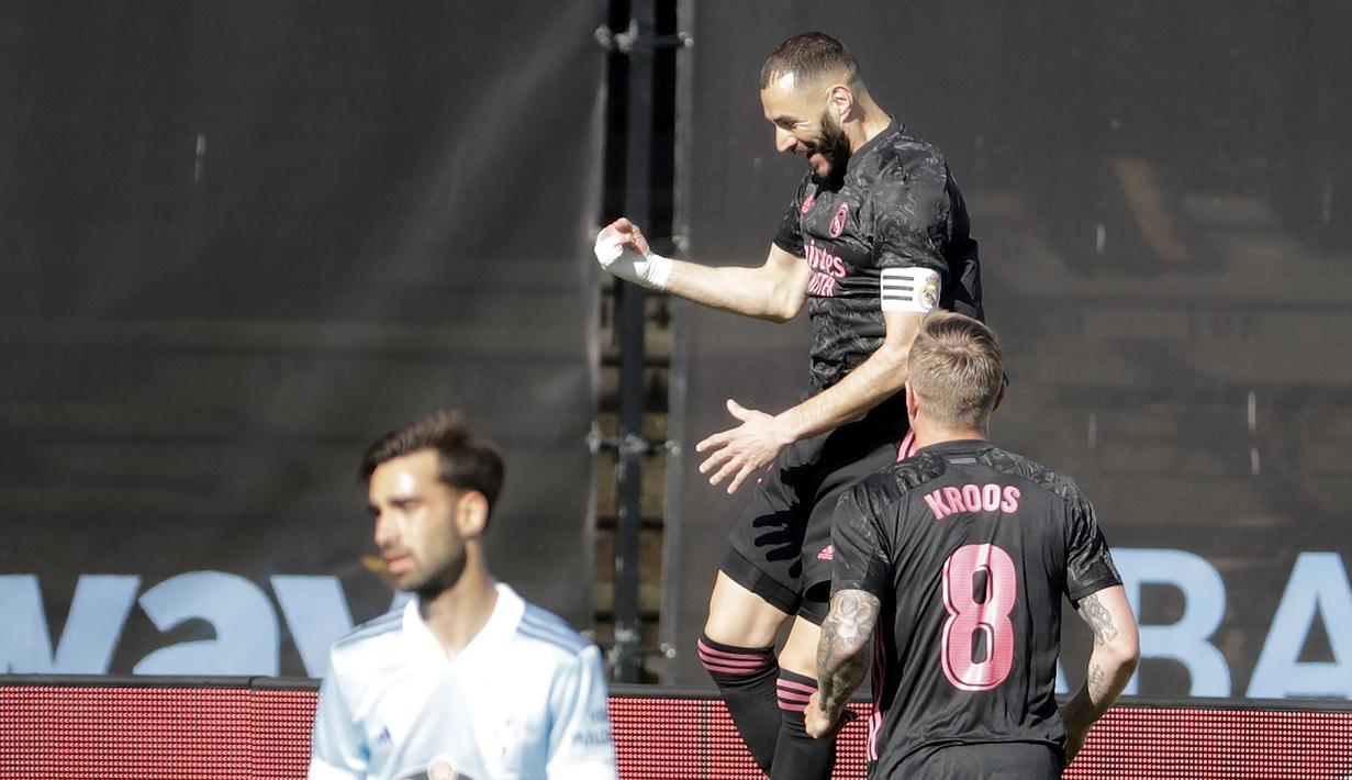 Striker Real Madrid, Karim Benzema (atas) melakukan selebrasi usai mencetak gol pertama timnya ke gawang Celta Vigo dalam laga lanjutan Liga Spanyol 2020/2021 pekan ke-28 di Balaidos Stadium, Sabtu (20/3/2021). Real Madrid menang 3-1 atas Celta Vigo. (AP/Lalo R. Villar)