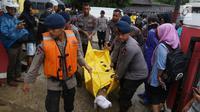 Polisi mengevakuasi jenazah korban gelombang Tsunami Anyer di Puskesmas Carita, Banten, Minggu (23/12). BNPB mencatat ratusan orang meninggal dunia dan ratusan luka-luka. (Liputan6.com/Angga Yuniar)