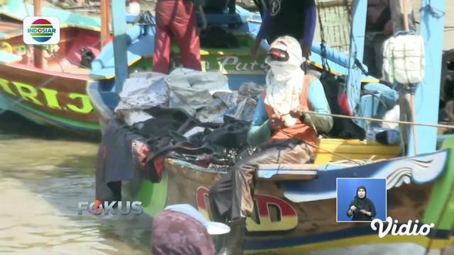 Warga Karawang bersihkan minyak mentah Pertamina yang tercecer di pesisir pantai menggunakan perahu.