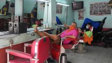 Tukang cukur menunggu pelanggan saat membuka kembali toko mereka setelah beberapa aktivitas bisnis diizinkan beroperasi kembali di Quezon, Filipina, Kamis (16/9/2021). Pemerintah memulai uji coba lockdown granular, di mana pembatasan ketat diterapkan untuk area yang lebih kecil. (AP/Aaron Favila)