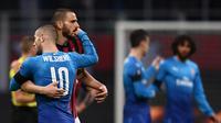 Bek AC Milan, Leonardo Bonucci berpelukan dengan pemain Arsenal, Jack Wilshere usai laga di Liga Europa. AC Milan kalah 0-2. (MARCO BERTORELLO / AFP)