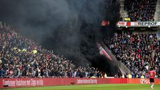 Asap hitam menyelimuti tribun penonton saat pertandingan sepak bola PSV Eindhoven vs Ajax dalam pertandingan Liga Eredivisie di Stadion Philips, Belanda (23/4). Asap hitam tebal tersebut sempat mengganggu jalannya pertandingan. (Olaf KRAAK / ANP / AFP)