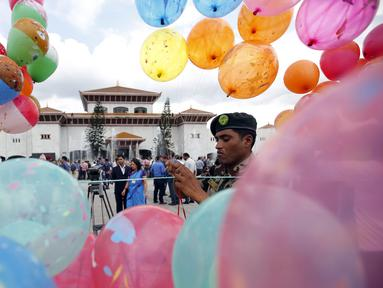 Seorang tentara memasang balon di depan gedung parlemen jelang Presiden Ram Baran Yadav resmi mengesahkan konstitusi baru di Kathmandu, Nepal, Minggu (20/9/2015). Nepal akan mengadopsi piagam demokratis secara penuh. (REUTERS/Navesh Chitrakar)