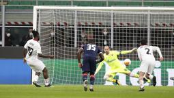 Gelandang AC Milan, Franck Kessie (kiri) melakukan eksekusi penalti yang berbuah gol ke gawang Red Star Belgrade dalam laga leg kedua babak 32 Besar Liga Europa 2020/21 di San Siro Stadium, Kamis (25/2/2021). AC Milan bermain Imbang 1-1 dengan Red Star Belgrade. (AP/Antonio Calanni)