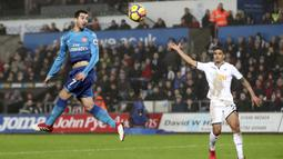 Aksi pemain Arsenal, Henrikh Mkhitaryan menyundul bola saat melawan Swansea City pada lanjutan Premier League di Liberty Stadium, Swansea, Wales, (30/1/2018). Arsenal kalah 1-3. (Nick Potts/PA via AP)