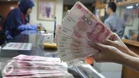 Seorang teller menunjukan  mata uang Yuan di Jakarta, Senin (30/11). Dana Moneter Internasional (IMF), Senin (30/11), resmi memasukan yuan, atau renminbi, ke dalam special drawing rights (SDR) sebagai mata uang elite dunia. (Liputan6.com/Angga Yuniar)