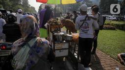 Pedagang ketupat sayur melayani pembeli saat berjualan di tengah aksi reuni 212, sekitaran Jalan Medan Merdeka Barat, Jakarta, Senin (2/12/2019). Sejumlah PKL meraup untung dengan berjualan di tengah ribuan massa Persaudaraan Alumni 212 yang mengikuti reuni di Monas. (Liputan6.com/Faizal Fanani)