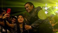 Didi kempot ketika diajak swafoto dengan para penggemarnya saat konser di Solo, Kamis malam (19/9).(Liputan6.com/Fajar Abrori)