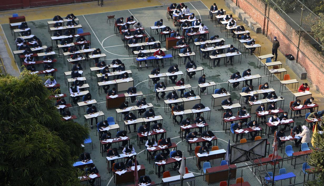 Siswa yang mengenakan masker mengikuti ujian kenaikan kelas XII di lapangan sekolah di Kathmandu, Nepal, Senin (23/11/2020). Nasib sekitar 450.000 siswa kelas XII digantung akibat COVID-19 saat ujian yang dijadwalkan mulai 20 April ditunda karena lockdown pada 24 Maret lalu. (PRAKASH MATHEMA/AFP)