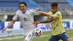 Penyerang Uruguay, Edinson Cavani, berebut bola dengan gelandang Kolombia, Wilmar Barrios, pada laga kualifikasi Piala Dunia 2022 zona CONMEBOL di Estadio Metropolitano Roberto Melendez, Sabut (14/11/2020) dini hari WIB. Uruguay menang 3-0 atas Kolombia. (AFP/Raul Arboleda)