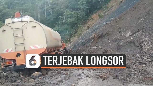 Sebuah mobil pengangkut bahan bakar minyak (BBM) terjebak di reruntuhan longsor di Mandailing Natal. Proses evakuasi dilakukan dengan bantuan kendaraan alat berat.