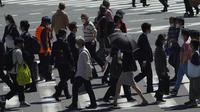 Orang-orang mengenakan masker untuk membantu mencegah penyebaran virus corona berjalan di sepanjang penyeberangan pejalan kaki di Tokyo (21/4/2021). Ibukota Jepang mengonfirmasi lebih dari 840 kasus virus corona baru pada hari Rabu. (AP Photo/Eugene Hoshiko)