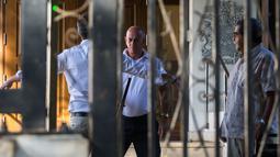 Petugas keamanan menggunakan detektor logam untuk memeriksa tamu di kedutaan besar Kanada di Hanava, Kuba, Selasa (17/3).  Kanada memulangkan staf diplomat beserta keluarga mereka dari Kuba karena terserang penyakit misterius. (AP/Desmond Boylan)