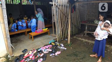 Seorang ibu melihat aktivitas belajar mengajar di Pendidikan Usia Dini (PAUD) Pelopor di Desa Cibeuteung, Ciseeng, Bogor, Rabu (19/2/2020). Sudah sejak 2009, PAUD yang memiliki 30 murid ini belajar pada bangunan sederhana menumpang di tanah milik orang lain. (merdeka.com/Arie Basuki)