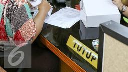 Petugas Sudin Pelayanan Pajak memberikan penjelasan alat traksaksi elektronic point of sales (e-pos), Jakarta, Selasa (16/2/2016). Target Sudin Pelayanan Pajak Jakarta Selatan Tahun 2016 sendiri  sebesar Rp2.132.846.000.000. (Liputan6.com/Yoppy Renato)
