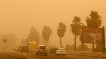 Kendaraan melintas di sepanjang jalan raya yang diselimuti debu tebal selama terjangan badai pasir di Kuwait City, Kuwait, pada 17 Juni 2021. Terjangan badai pasir ini membuat jarak pandang atau visibilitas di beberapa daerah turun hingga kurang dari 100 meter. (AFP/YasserAl-Zayyat)