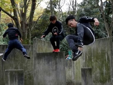 Juni Sato bersama rekan-rekannya beraksi unjuk kemampuan melakukan parkour di sebuah taman di Tokyo, Jepang (2/11). Karena cintanya dengan seni olahraga ekstrem ini, Sato mendirikan sekolah parkour yang diberi nama SENDAI X-TRAIN. (Reuters/Kim Kyung-Hoon)