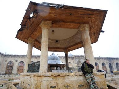 Seorang anggota pasukan Presiden Suriah Bashar al-Assad berdiri di salah satu bangunan yang berada di kompleks Masjid Umayyad, Aleppo di Suriah, 13 Desember 2016. Masjid ini menjadi salah satu masjid tertua di dunia. (REUTERS/Omar Sanadiki)