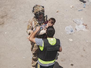 Tentara AS membawa seorang anak di pos pemeriksaan selama evakuasi di Bandara Internasional Hamid Karzai di Kabul, Jumat (20/8/2021). Sejumlah ibu Afghanistan berupaya menyerahkan bayi-bayi mereka pada tentara asing yang berjaga di bandara. (Staff Sgt. Victor Mancilla/U.S. Marine Corps via AP)