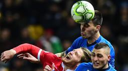 Striker Liechtenstein, Nicolas Hasler, duel udara dengan pemain Italia, Alessio Romagnoli dan Marco Verratti pada laga Kualifikasi Piala Eropa 2020 di Stadion Ennio-Tardini, Selasa (26/3). Italia menang 6-0 atas Liechtenstein. (AFP/Miguel Medina)
