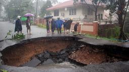 Orang-orang melihat lubang besar di jalan yang disebabkan setelah banjir di Mawlamyein, negara bagian Mon (9/8/2019). Hujan lebat yang menguyur Myanmar membuat banjir di beberapa wilayah dan memaksa puluhan ribu warga diungsikan dari rumah mereka. (AFP Photo/Chit Ko Lin)