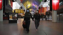 Pasangan berjalan melewati Fremont Street yang sepi setelah perintah penutupan kasino akibat virus corona COVID-19 di Las Vegas, Amerika Serikat, Rabu (18/3/2020). Penutupan tempat hiburan di Las Vegas akan berlangsung selama 30 hari. (AP Photo/John Locher)