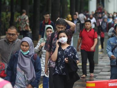 Pekerja berjalan kaki saat jam pulang di kawasan Sudirman, Jakarta, Jumat (7/2/2020). BPJS Ketenagakerjaan yang kini bernama BP Jamsostek menargetkan sekitar 23,5 juta tenaga kerja baru masuk dalam daftar kepesertaan pada 2020. (Liputan6.com/Angga Yuniar)