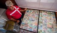 Pria Serbia, Zoran Milosevic dengan koleksi uang kertas dan koin dari seluruh dunia di rumahnya desa Pavlovci, Belgrade, 10 September 2018. Selama 36 tahun, pria yang bekerja sebagai tukang kunci itu mengumpulkan mata uang dunia. (AFP/ANDREJ ISAKOVIC)
