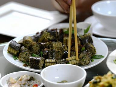Foto pada 24 Agustus 2018 memperlihatkan pelanggan menyantap olahan daging ular di sebuah restoran khusus provinsi Yen Bai, Vietnam. Daging ular menempati peringkat pertama sebagai hidangan ekstrem yang digemari banyak orang Vietnam. (AFP/Nhac NGUYEN)