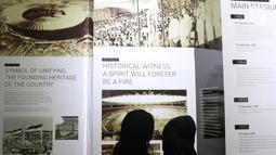 Pengunjung melihat-lihat dokumentasi pembangunan kompleks olahraga Gelora Bung Karno yang dipamerkan di area Stadion GBK, Jakarta, Rabu (29/8). Sejumlah dokumentasi pembangunan stadion dicetak dan bisa dilihat warga. (Liputan6.com/Helmi Fithriansyah)