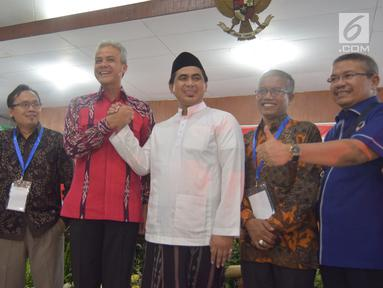 Calon Gubernur Jawa Tengah, Ganjar Pranowo berjabat tangan dengan wakilnya Cawagub Taj Yasin saat mendaftar di KPUD Jateng, Semarang, Selasa (9/1). Pendaftaran paslon ini dilakukan di hari kedua waktu pendaftaran. (Liputan6.com/Gholib)