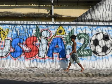 Seorang anak laki-laki melewati mural Piala Dunia 2018 di dinding jalanan Camboata, Rio de Janeiro, Brasil, Kamis (31/6). (Fabio TEIXEIRA/AFP)